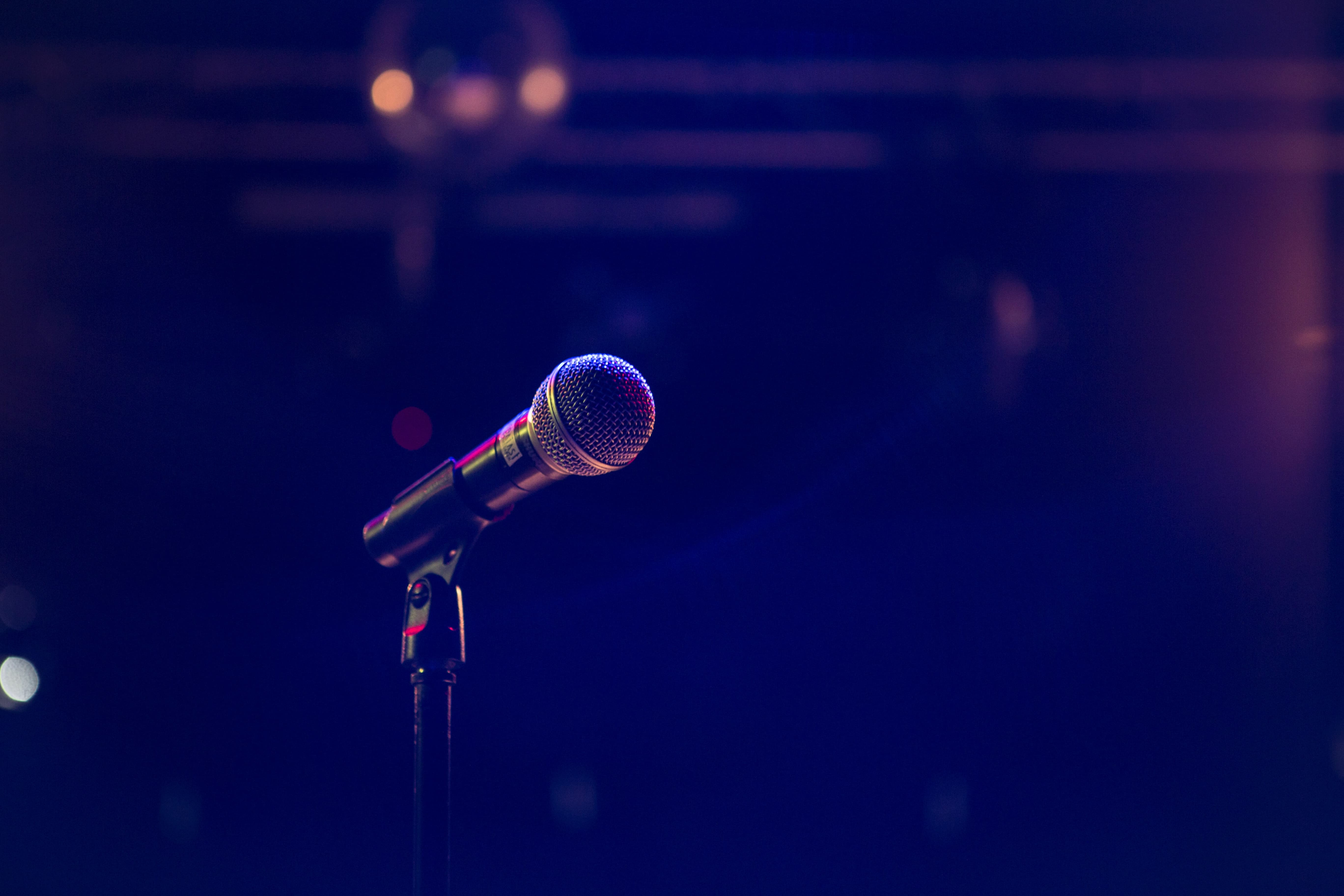 A microphone on a stand set along on a dramatically lit stage